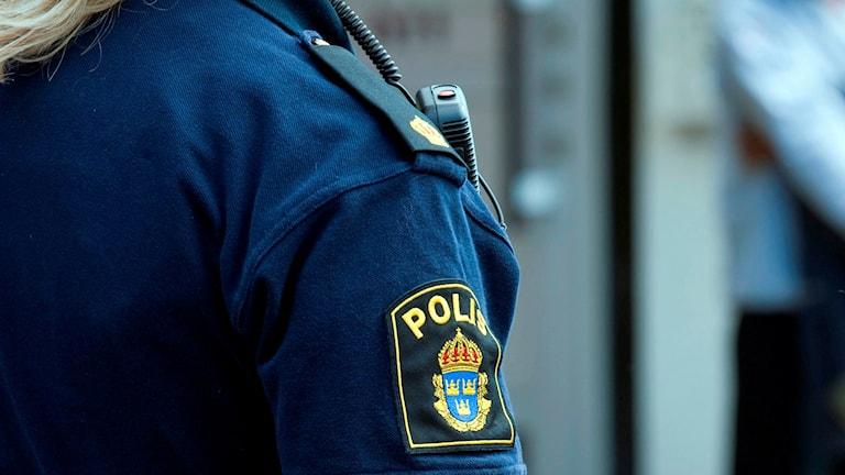 Axeln med polisemblem på kvinnlig polis