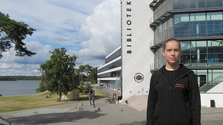 Victoria Vucic framför BTH byggnaden i Karlskronam med havet i bakgrunden.Foto: Sarah Rätzer/Sveriges Radio.