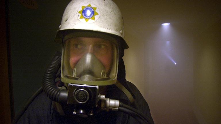 En brandman med mask på i ett rökfyllt rum. Foto: Björn Larsson/TT