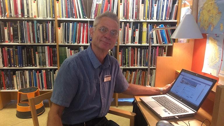 Energirådgivare Lars Ivarsson sitter framför en bokhylla med böcker. Foto: Lena König.