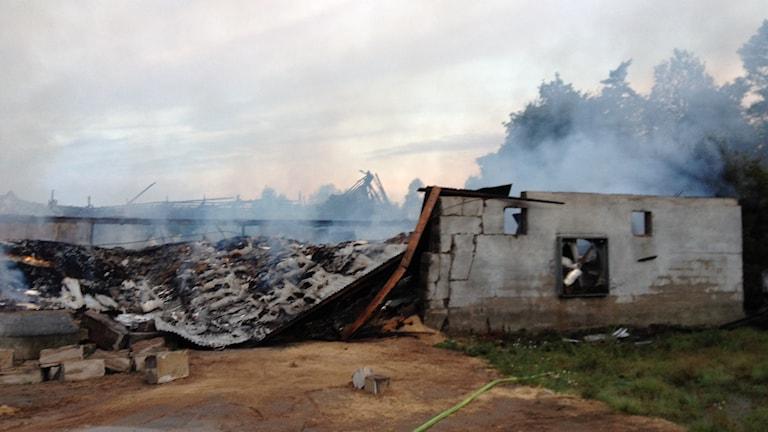 Sönderbrända ladan efter brand med rök i bakgrunden. Foto: Rebecka Gyllin/Sveriges Radio