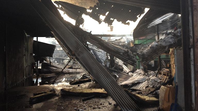 Inifrån den nerbrända ladan hänger delar av taket ner. Foto: Rebecka Gyllin/Sveriges Radio