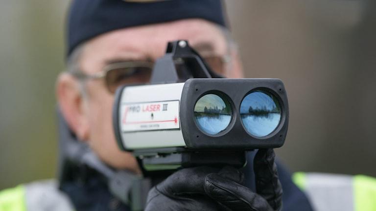 En polis som skjuter med lasermätare i trafiken. Foto: Fredrik Sandberg/TT.