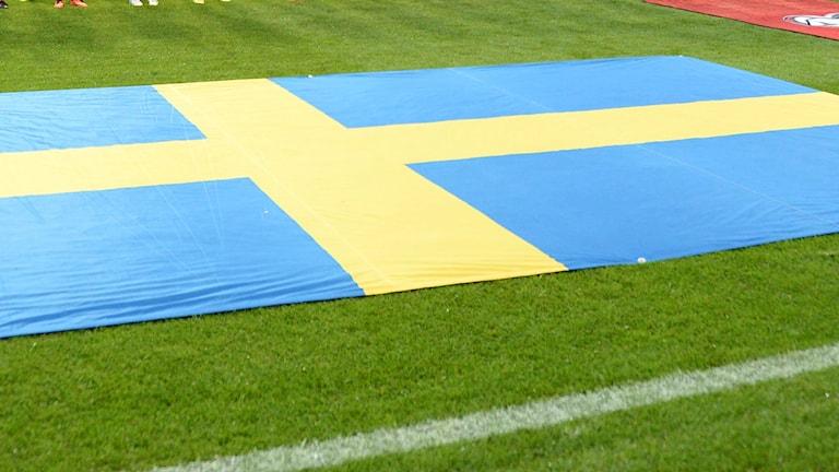 Svenska flaggan utlagd på en fotbollsplan.