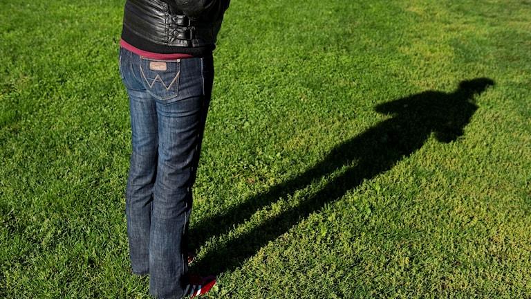 Kvinna står på gräsmatta
