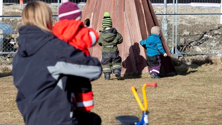 Barn leker på dagis med personal utomhus.