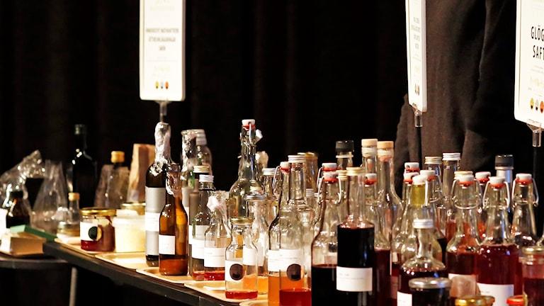 Allehanda glasflaskor i olika storlekar, fyllda med dryck, står uppradade på ett bord.