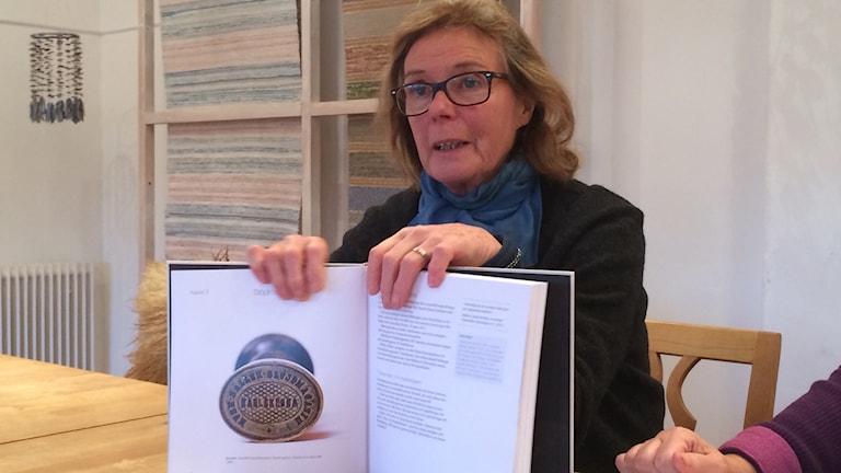 Birgitta Olving håller upp den nya boken. Foto: Lena König/Sveriges Radio.