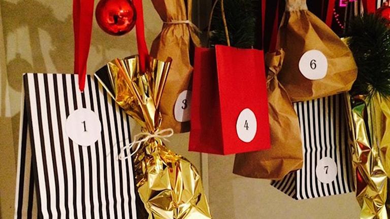 Flera paket som hänger i en julkalender. Foto: Sveriges Radio.