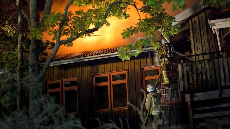 En brandman försöker släcka en brand i ett hus. Foto: Björn Larsson Rosvall/TT