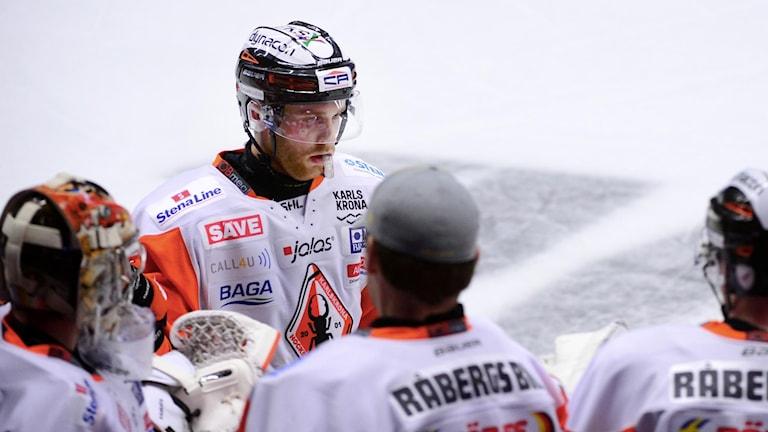 KHK-spelaren Mattias Guter står på isen och pratar med lagkamrater. Foto: Robert Granström/TT
