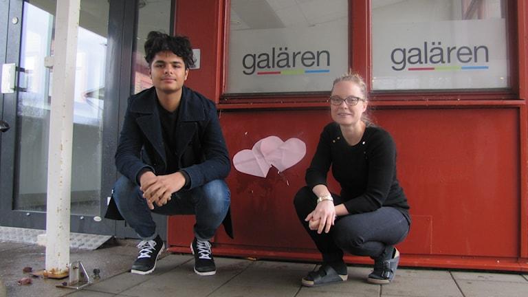 Mohammed Kadhim Abed och läraren Karin Falkbrink sitter vid en vägg med hjärtan på. Foto: Sarah Rätzer/Sveriges Radio.