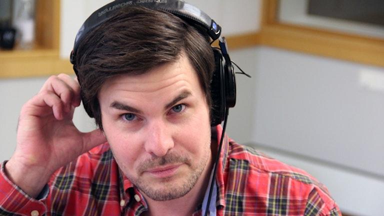 En porträttbild av Samuel Martinsson som sitter i studion. Foto: Stina Linde/Sveriges Radio.