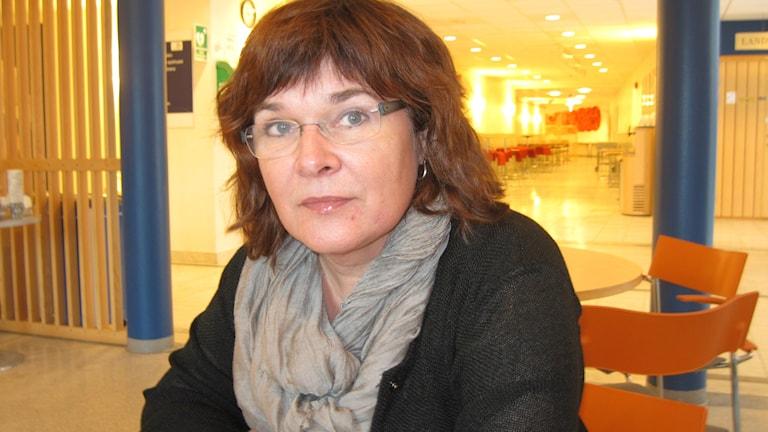 Karin Nogren sitter vid ett bord i cafeterian i Wämö Center. Foto: Anna Börje/Sveriges Radio