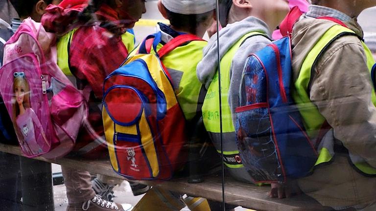 Barn med ryggsäckar, bara ryggar syns.