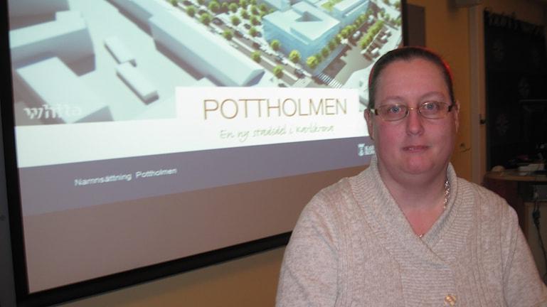 Suzanne står framför en arktiektbild över det nya kvarteret Pottholmen