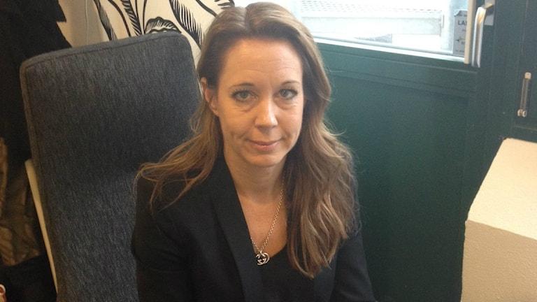 Anna Wallin sitter bakom skrivbordet på sitt kontor.