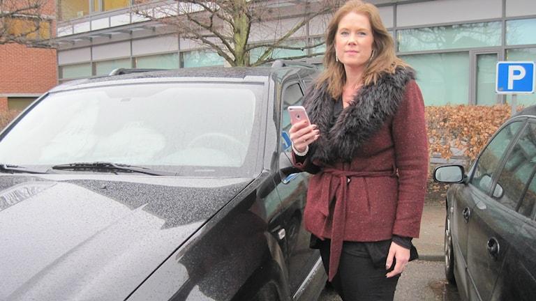 Linda Nejdefelt står framför en parkering bil med sin mobil i handen.