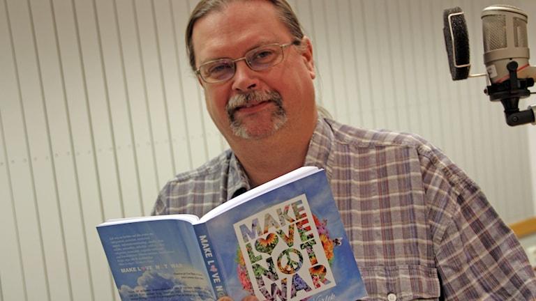 Per Drysén från olofström håller upp antologin som han medverkar i. Foto: Stina Linde/Sveriges Radio.