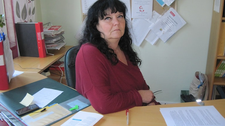 Maria sitter bakom skrivbordet på sitt kontor