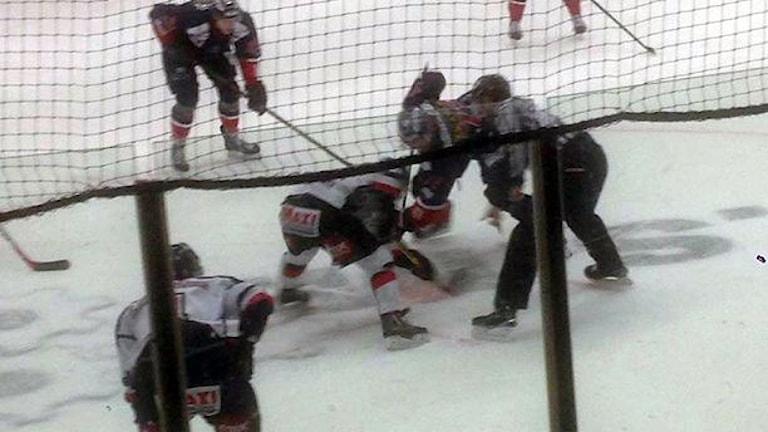 Flera hockeyspelare på isen slåss om pucken. Foto: Elias Holgersson/Sveriges Radio.