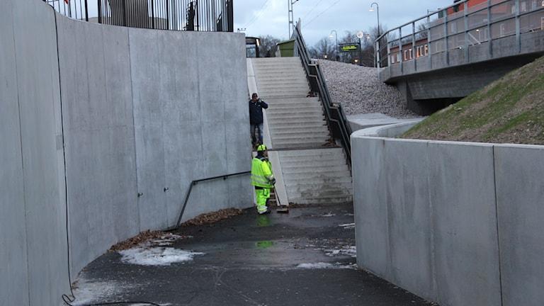 En av kommunens anställda sopar undan det sista av vattnet i tunneln vid Bergåsa. Foto: Stina Linde/Sveriges Radio.