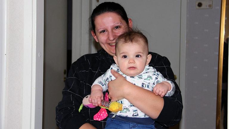 Sandra Karlsson håller upp sin dotter Meya. Foto: Stina Linde/Sveriges Radio.