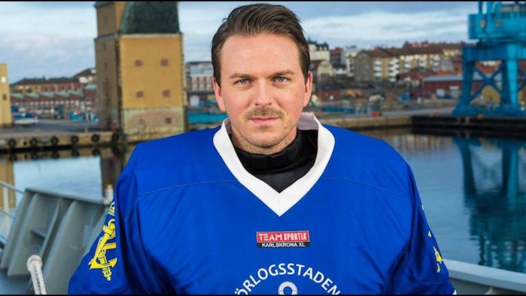 Hockeyspelaren Thomas Nord står på ett fartyg med Karlskrona varvskranar i bakgrunden. Foto: Christoffer Enarsson