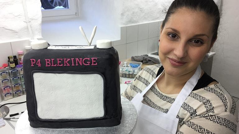 En kvinna står och håller i en tårta som liknar en radioapparat. Foto: Rebecka Gyllin/Sveriges Radio