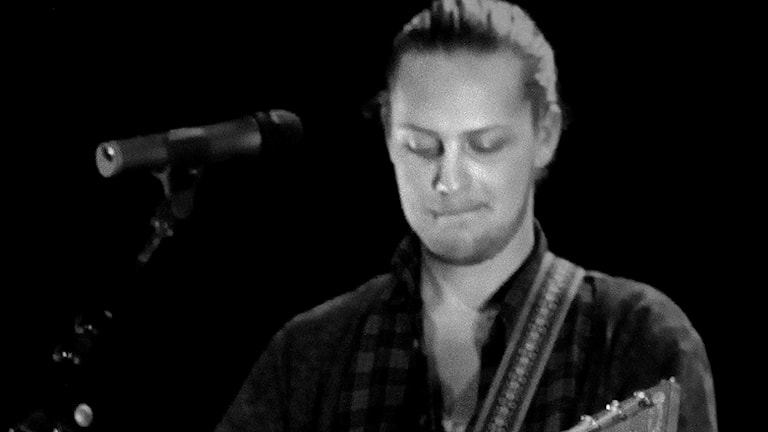 Frontmannen i At Horse spelar gitarr på en scen. Foto: Oskar Sandström.