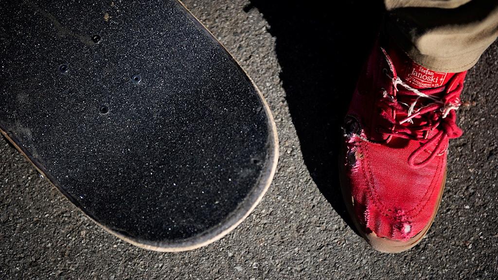 En skateboard och en sko brevid.