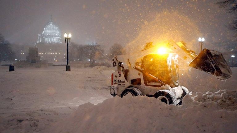 En snöslunga röjer snö i Washington och har Kapitolium i bakgrunden. Foto: Alex Brandon/TT