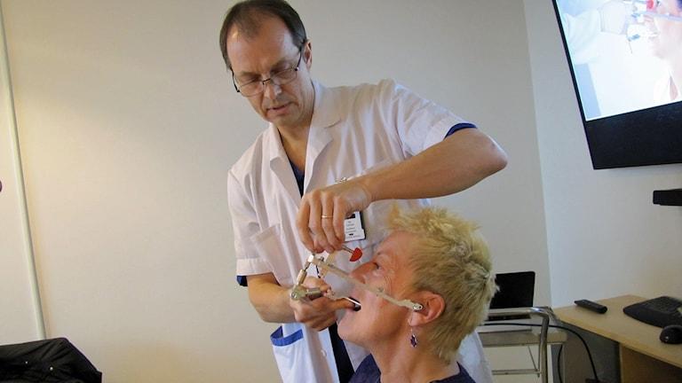 Övertandläkaren Per Carlsson mäter käkrörelserna på verksamhetschefen Monica Palmö med hjälp av en ansiktsbåge. Foto: Sarah Rätzer / Sveriges Radio