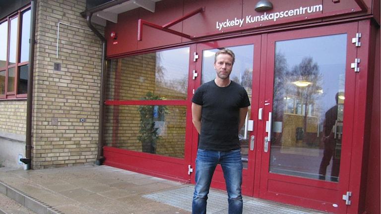 En man står vid ingången till Lyckeby Kunskapscentrum. Foto: Sarah Rätzer/Sveriges Radio