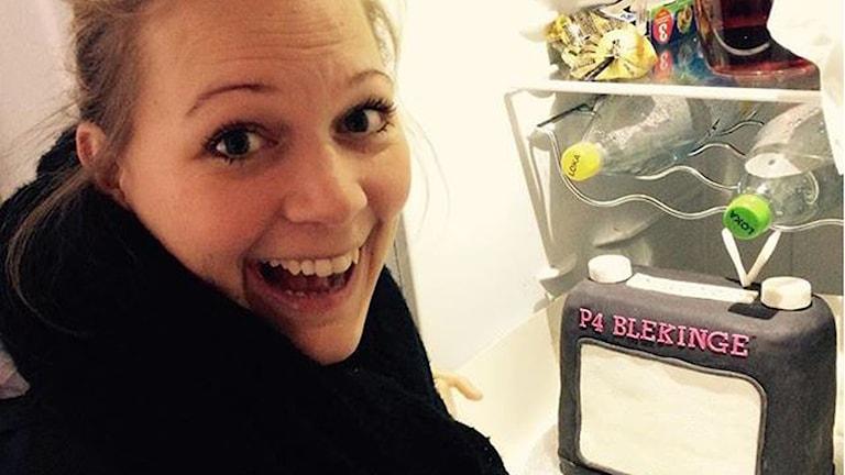 En bild på Rebecka Gyllin framför en tårta som det står P4-Blekinge på. Foto: Stina Linde/Sveriges Radio.
