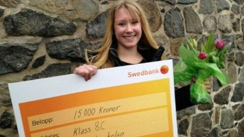 Rebecka Haraldsson håller upp en check på 15 000 kronor och håller blommor i andra handen. Hon har ett stort leende på läpparna.
