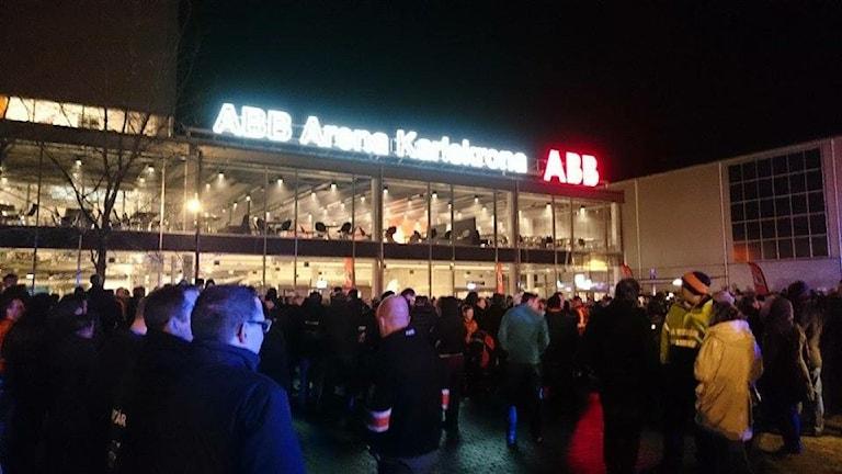 En stor folksamling står i mörkret utanför ABB arena i Karlskrona.