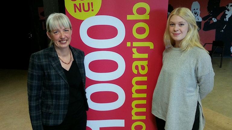 """Två glada kvinnor står framför en banner med orden """"1000 sommarjobb"""" på."""