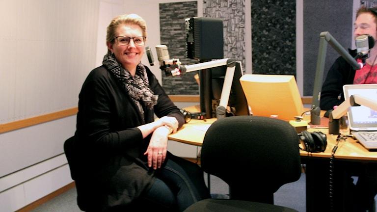 Anna Svahn i studion framför en av mikrofonerna.
