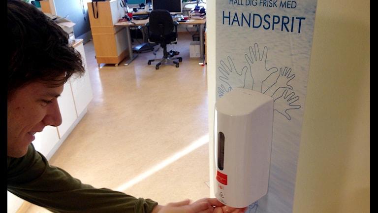 Anton Vretander smörjer in händerna med handsprit.