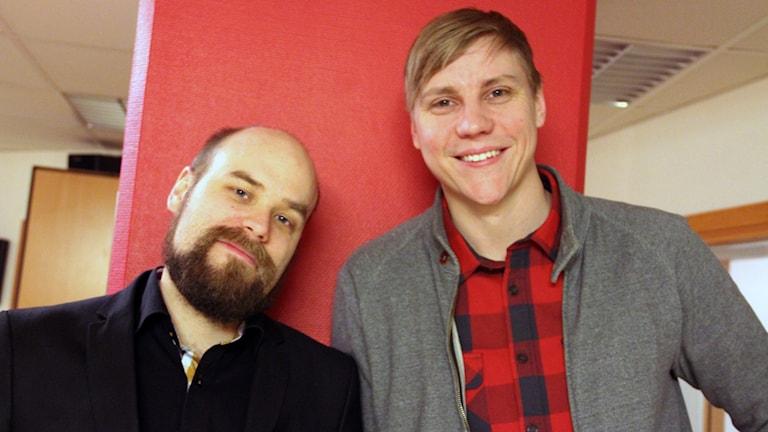 Henrik Harrysson och Mathias Roos framför en röd vägg.