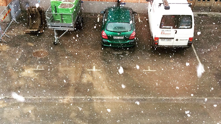Snöflingor i luften vid en parkering.