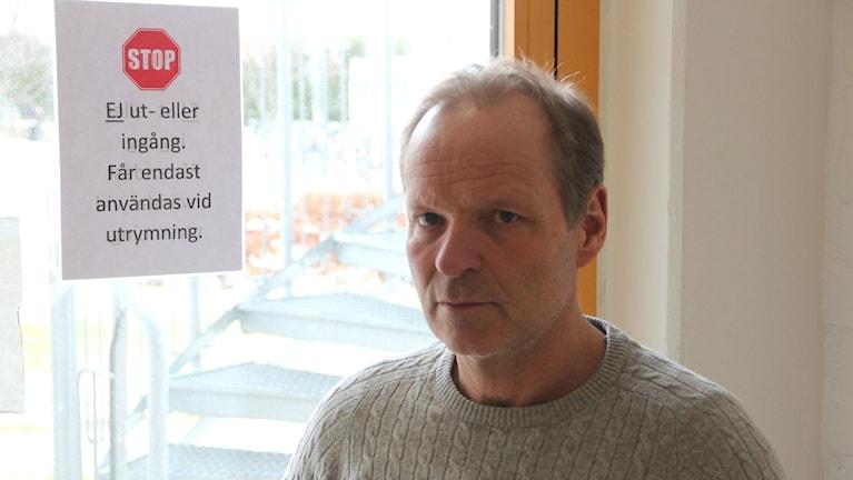 Skolområdeschef Ronny Mattsson vid en låst dörr med en stoppskylt klistrad på
