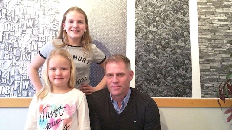 Två unga tjejer bredvid en vuxen man.