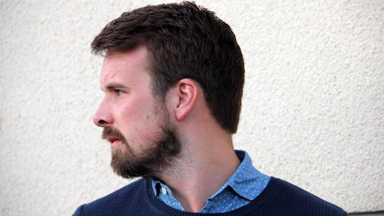 Erik Belin tittar åt sidan framför en vit vägg
