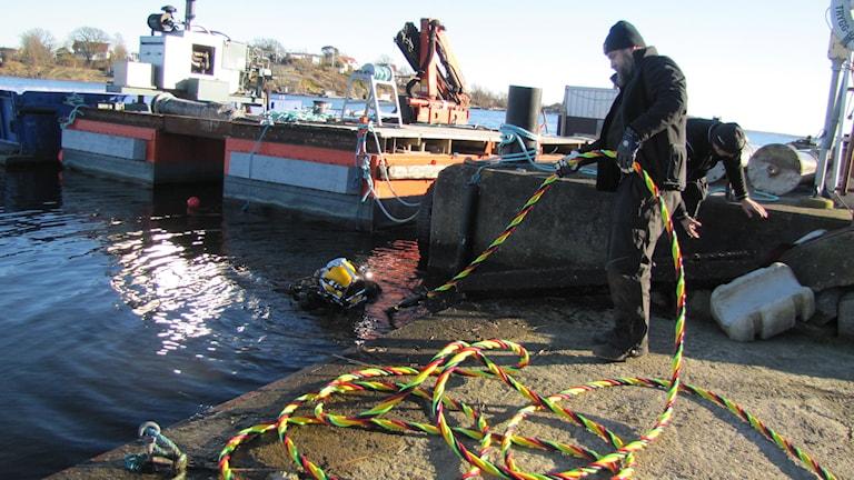 En dykare i dykardräkt  inspekterar i vattnet och två dykare står på land och håller i ett rep som dykaren sitter fast i.