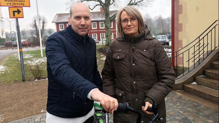En man och en kvinna står och håller i en cykel.