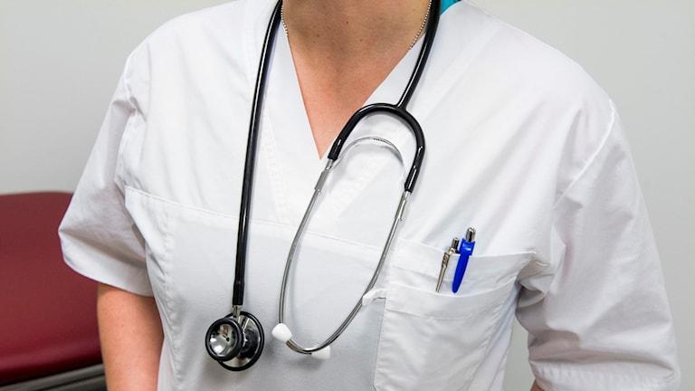 Överkroppen på en läkare med stetoskop runt halsen.