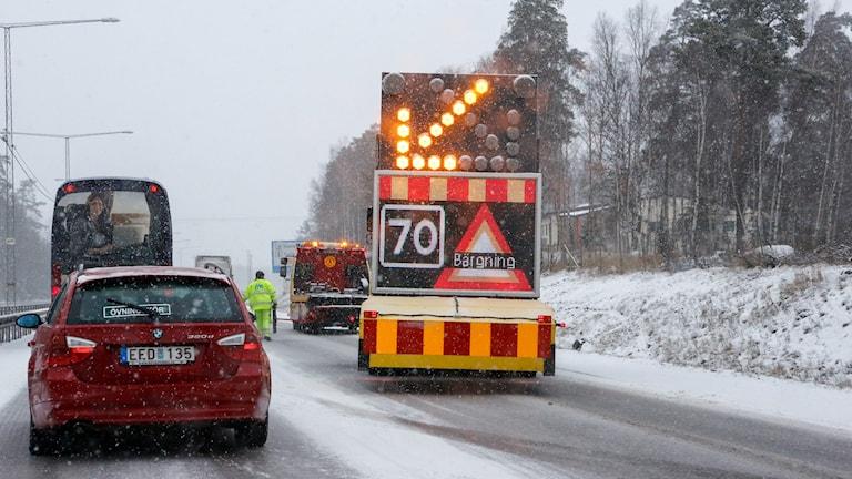 Varningsskylt för bärgning och en uppmaning att sänka hastigheten på en snöig väg.