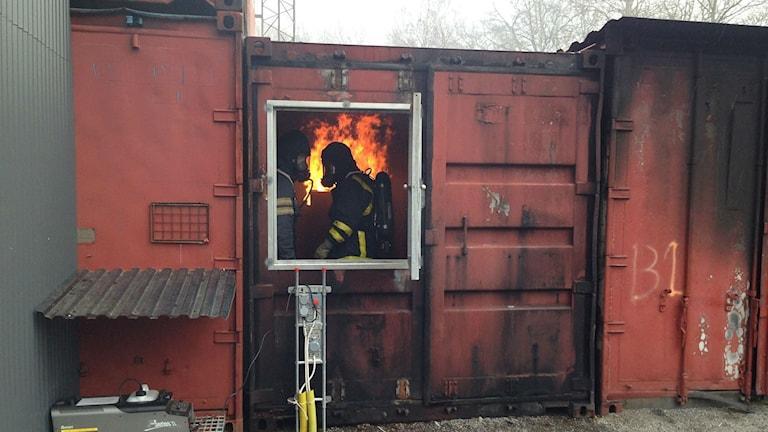 Brandmän går runt inne i en byggnad där det brinner.